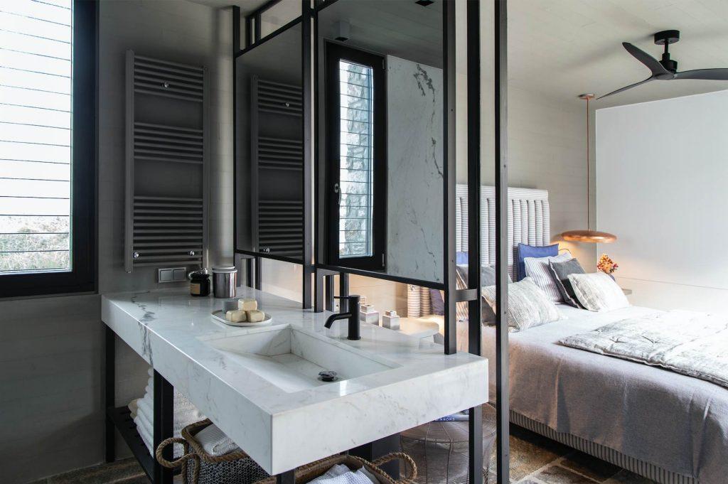 Łazienka z przepierzeniem w formie ściany z luster i umywalki nadaje lekkość i zyskuje przestrzeń.